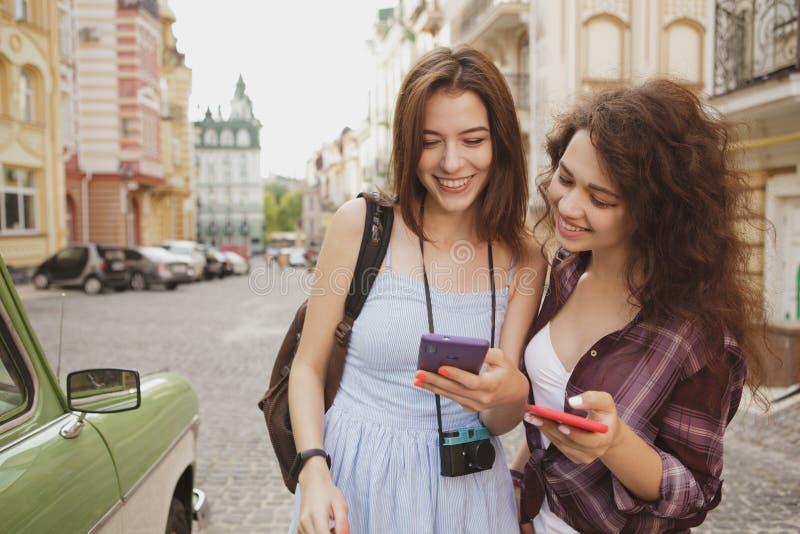 Amigos femeninos jovenes que disfrutan de viajar junto, usando mapa en la ciudad fotos de archivo