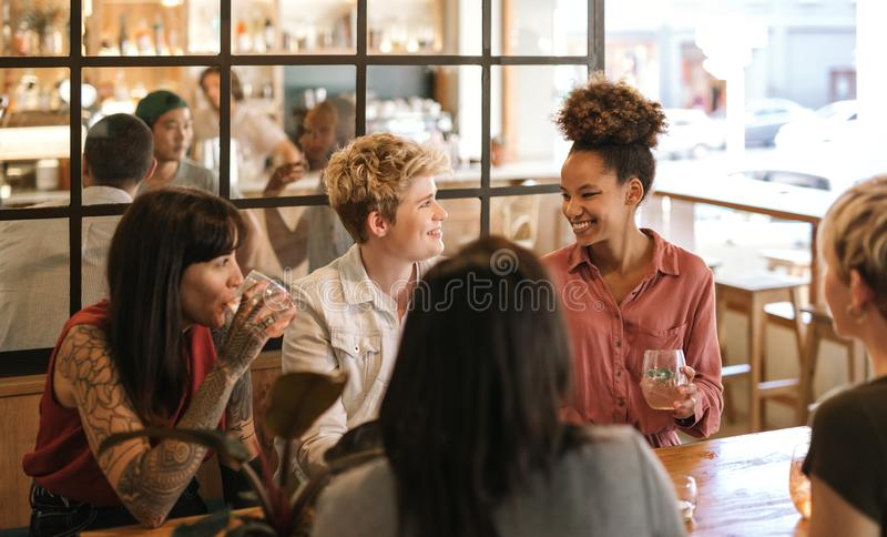 Amigos femeninos jovenes que ríen junto sobre bebidas en un bistro fotografía de archivo