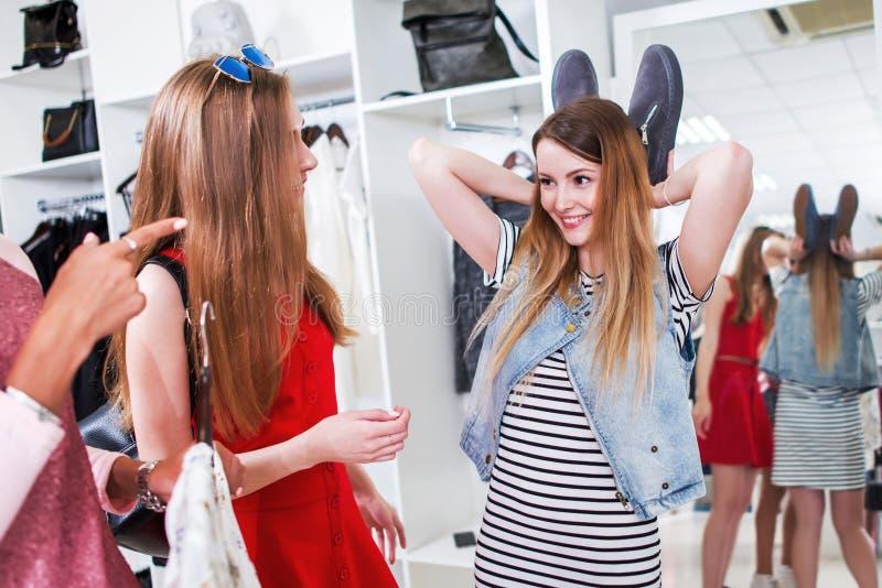 Amigos femeninos jovenes que se divierten mientras que hace compras en tienda de ropa Muchacha bonita que usa sus zapatos para mo imagenes de archivo