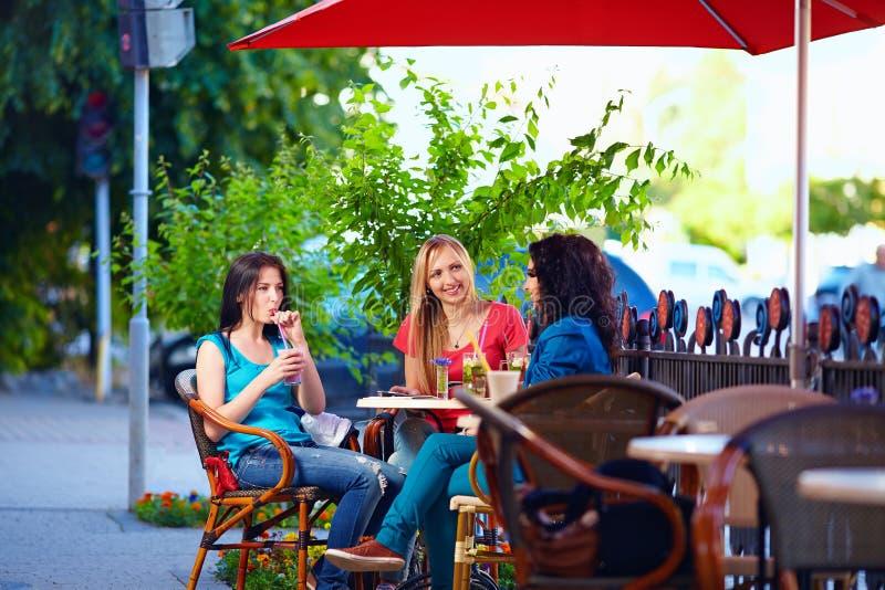 Amigos femeninos jovenes que se sientan en terraza del café, al aire libre imagenes de archivo
