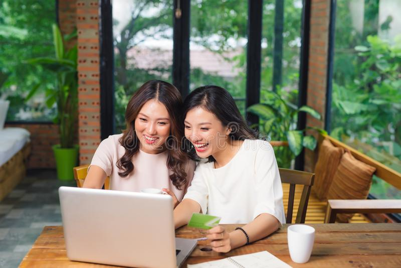 Amigos femeninos jovenes relajados felices que hacen compras en línea a través fotografía de archivo libre de regalías