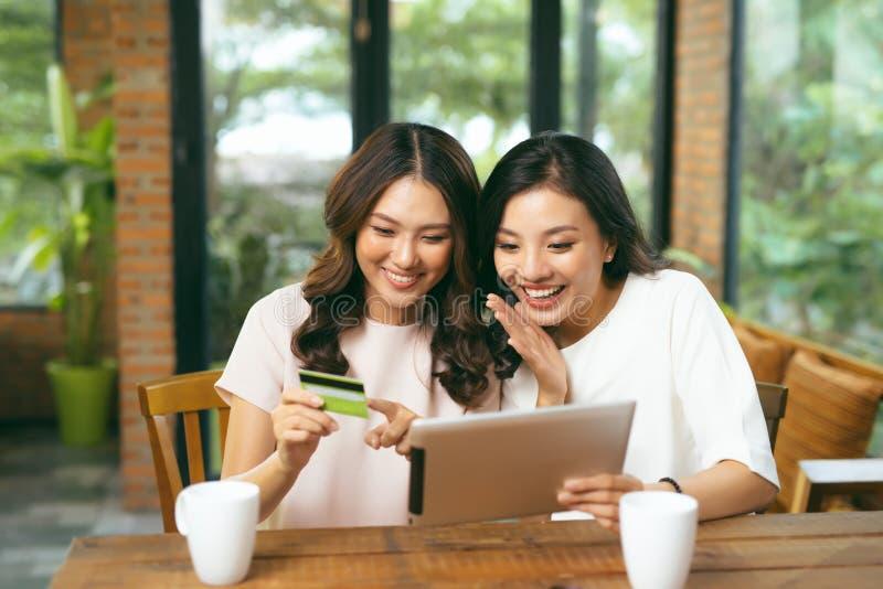 Amigos femeninos jovenes relajados felices que hacen compras en línea a través foto de archivo libre de regalías