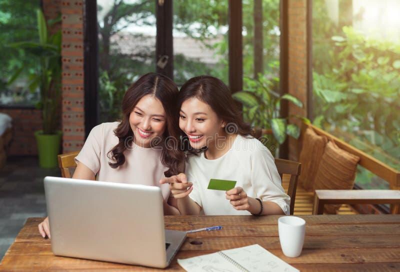 Amigos femeninos jovenes relajados felices que hacen compras en línea a través imagenes de archivo