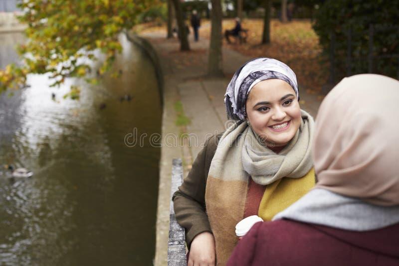 Amigos femeninos musulmanes británicos que hablan por el río en ciudad fotos de archivo libres de regalías