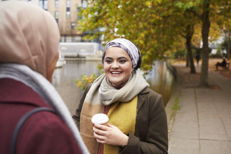 Amigos femeninos musulmanes británicos que hablan por el río en ciudad fotografía de archivo