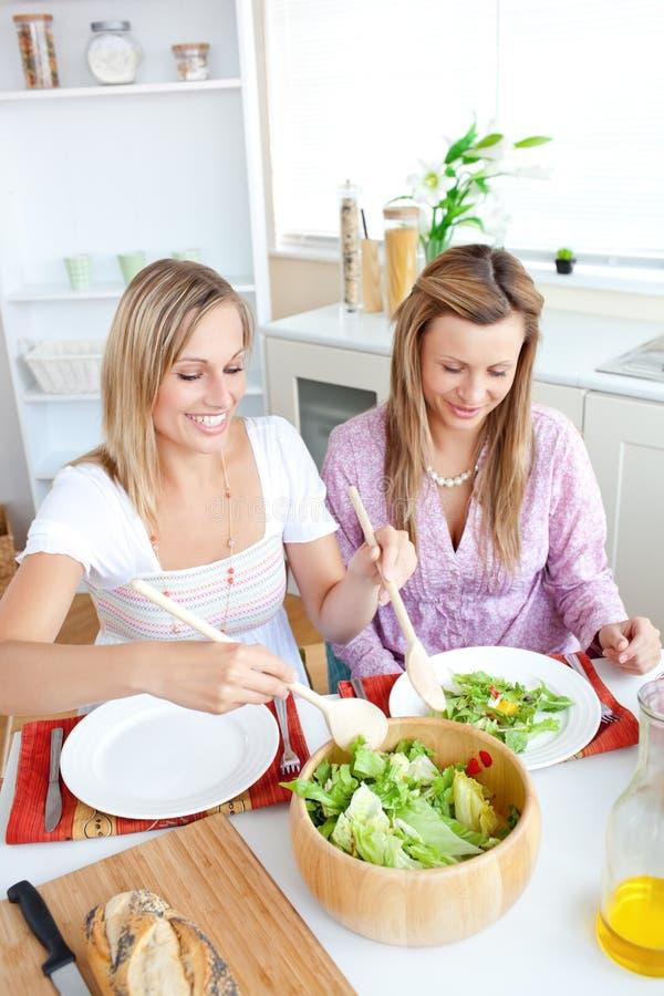 Amigos femeninos que brillan intensamente que comen la ensalada en la cocina imagenes de archivo