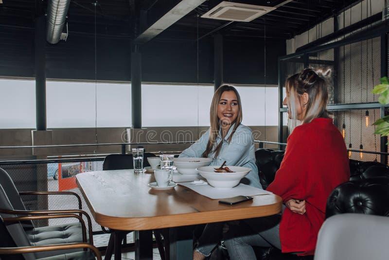 Amigos femeninos que hablan en el café, comiendo el almuerzo foto de archivo