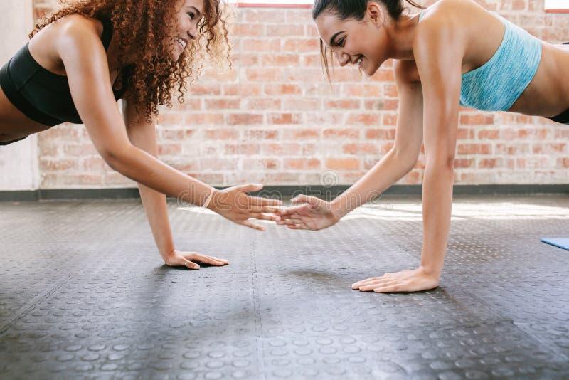 Amigos femeninos que hacen flexiones de brazos juntas foto de archivo libre de regalías