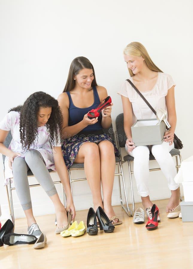 Amigos femeninos que intentan en nuevo calzado en casa fotos de archivo libres de regalías