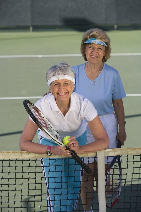 Amigos femeninos que juegan dobles en el campo de tenis fotos de archivo libres de regalías
