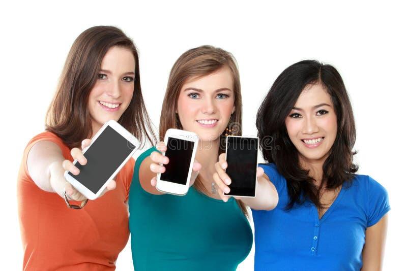 Amigos femeninos que muestran sus teléfonos móviles fotos de archivo