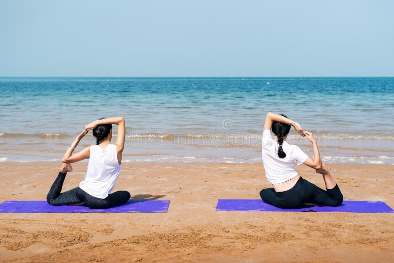Amigos femeninos que practican yoga en la playa imagenes de archivo