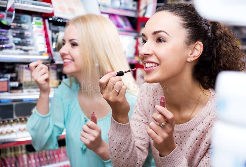 Amigos femeninos que seleccionan lustre del labio imagen de archivo