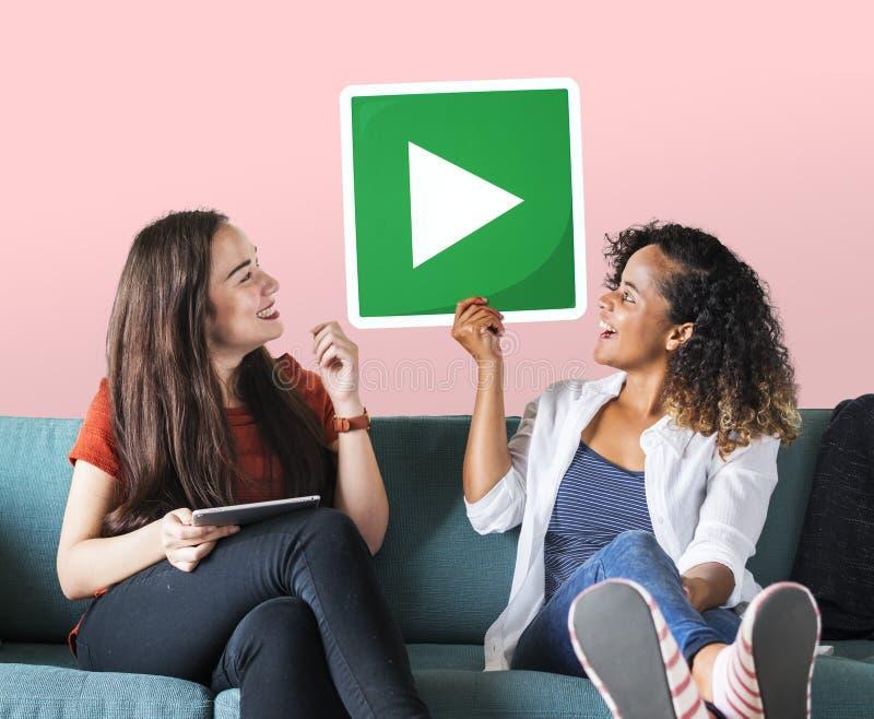 Amigos femeninos que sostienen un botón de reproducción imagen de archivo libre de regalías
