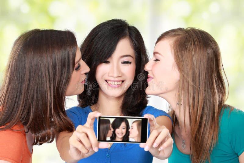 Amigos femeninos que toman una imagen de ellos mismos imagen de archivo