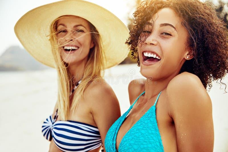 Amigos femeninos sonrientes en bikinis que broncean en una playa arenosa imagenes de archivo