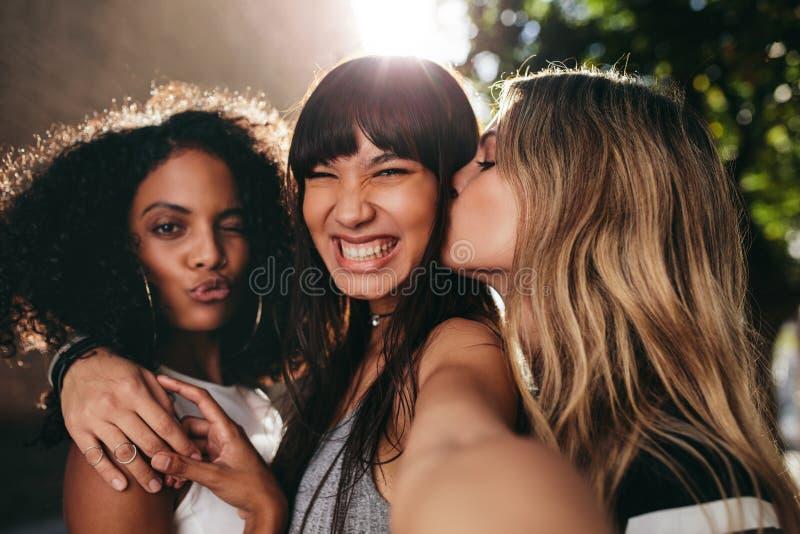 Amigos femeninos sonrientes que cuelgan hacia fuera junto y tomar el selfie imagenes de archivo