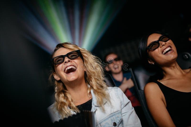 Amigos femeninos sonrientes que miran la película 3d imagen de archivo libre de regalías