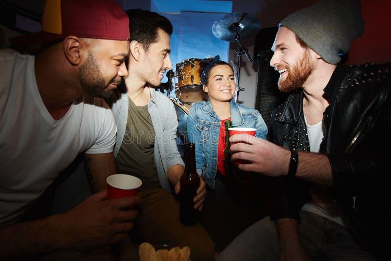 Amigos frescos que se enfrían con la cerveza en el partido del club de noche fotos de archivo