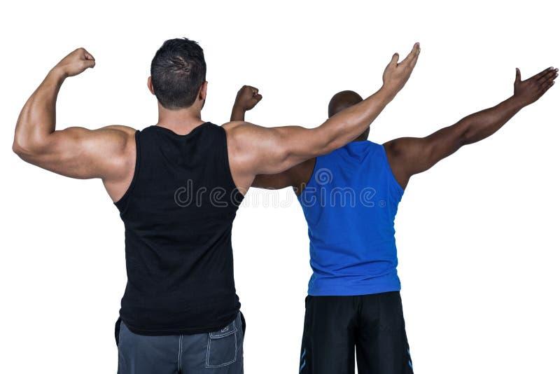 Amigos fuertes que presentan con los brazos hacia fuera fotografía de archivo