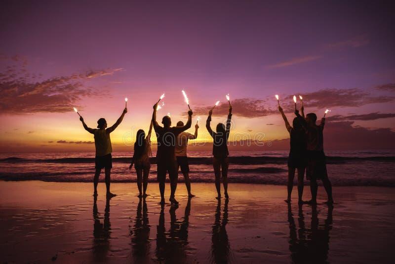Amigos grandes del grupo con las luces de la chispa en la playa imagenes de archivo