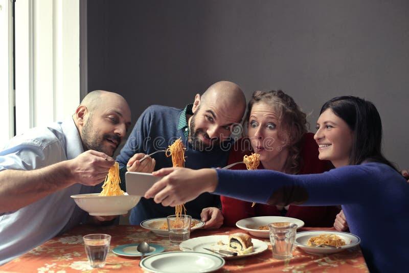 Amigos hambrientos que comen los espaguetis imagenes de archivo