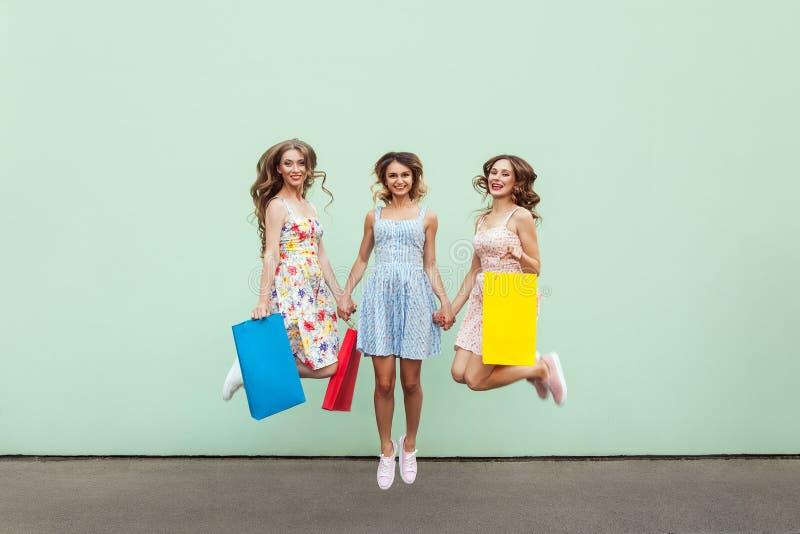 Amigos hermosos de la felicidad tres que saltan de feliz con los paquetes coloridos después de hacer compras fotos de archivo libres de regalías