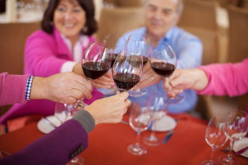 Amigos idosos que dizem elogios com vinho tinto fotografia de stock royalty free