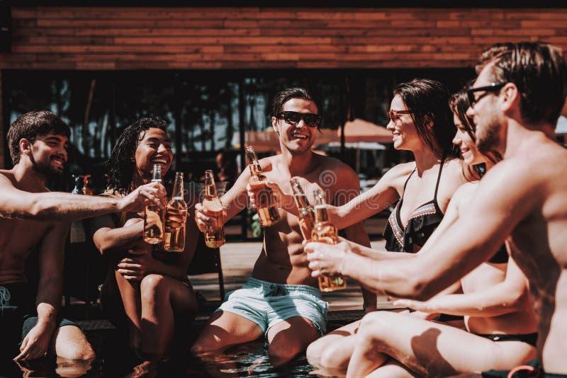Amigos jovenes con las bebidas alcohólicas en el Poolside fotografía de archivo libre de regalías