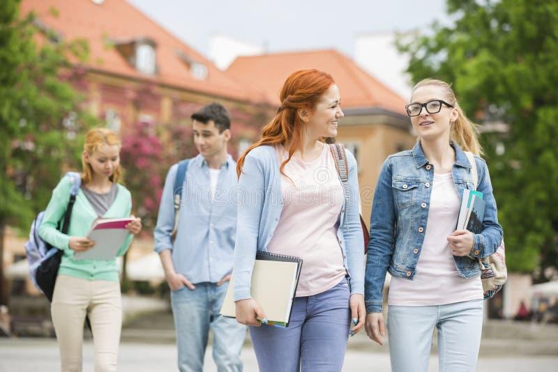 Amigos jovenes de la universidad que caminan en la calle fotos de archivo