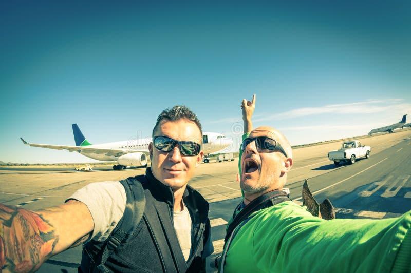Amigos jovenes del inconformista moderno que toman un selfie en el aeropuerto imagenes de archivo