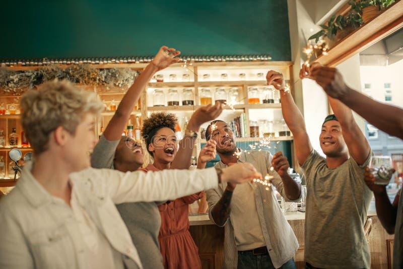 Amigos jovenes diversos que celebran en una barra con las bengalas imagen de archivo