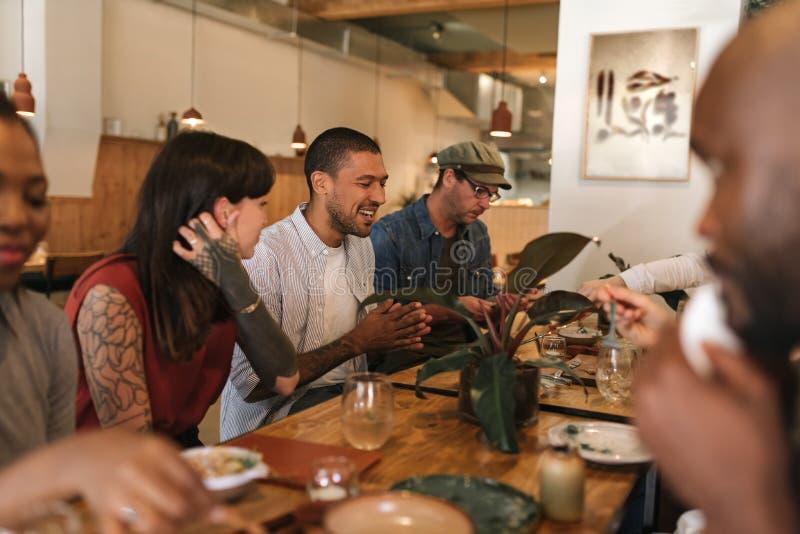 Amigos jovenes diversos que se divierten junto sobre una cena de los bistros imagen de archivo