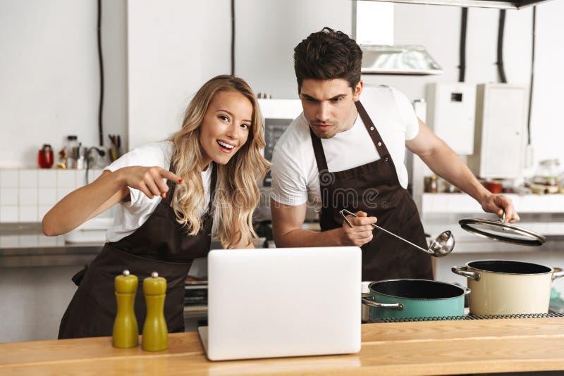 Amigos jovenes emocionales que aman a los cocineros de los pares en la cocina que cocinan usando el ordenador portátil fotos de archivo