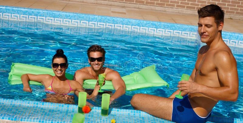 Amigos jovenes en la sonrisa de la piscina fotografía de archivo
