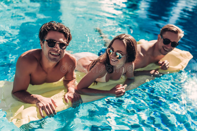 Amigos jovenes en piscina fotos de archivo