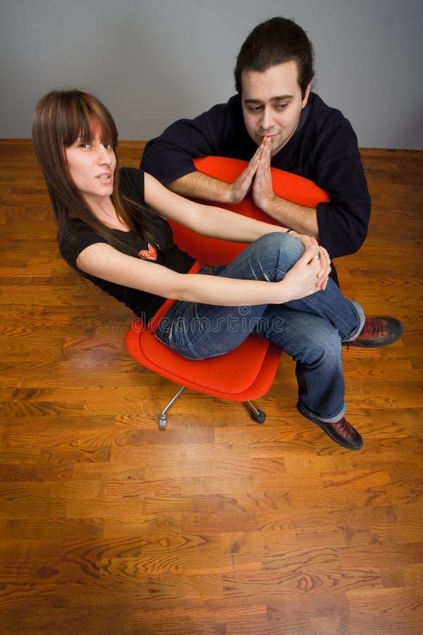 Amigos jovenes en silla roja imagen de archivo
