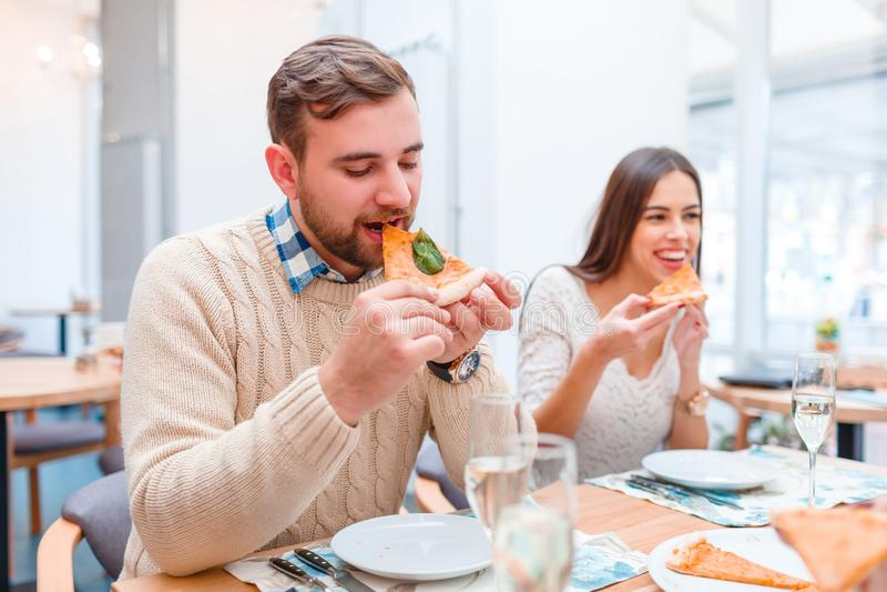 Amigos jovenes enjoing la comida en buen restaurante fotos de archivo