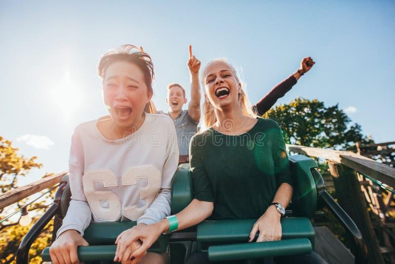 Amigos jovenes entusiastas que montan paseo del parque de atracciones foto de archivo