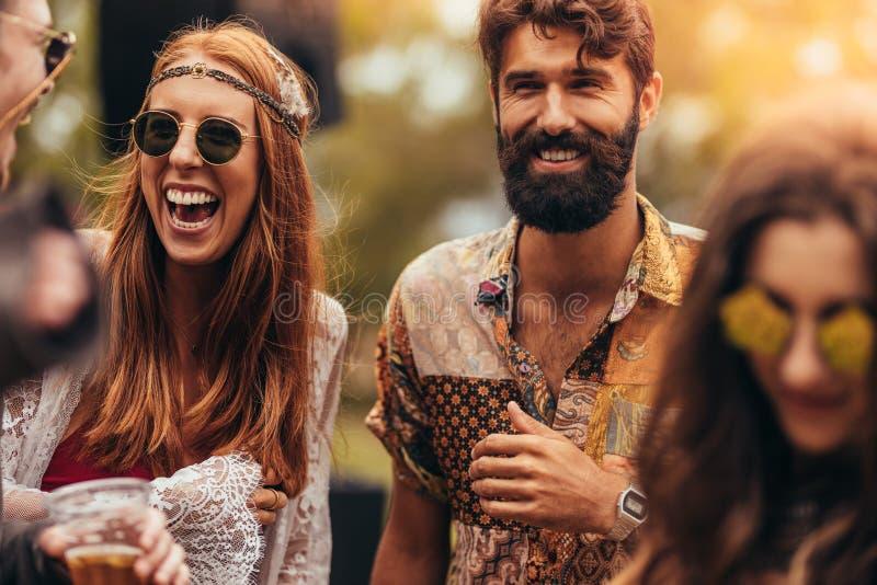 Amigos jovenes felices del hippie en el festival de música fotografía de archivo libre de regalías