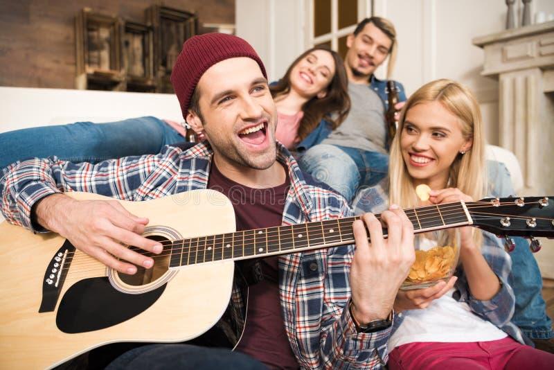 Amigos jovenes felices que gozan de la guitarra en casa fotografía de archivo