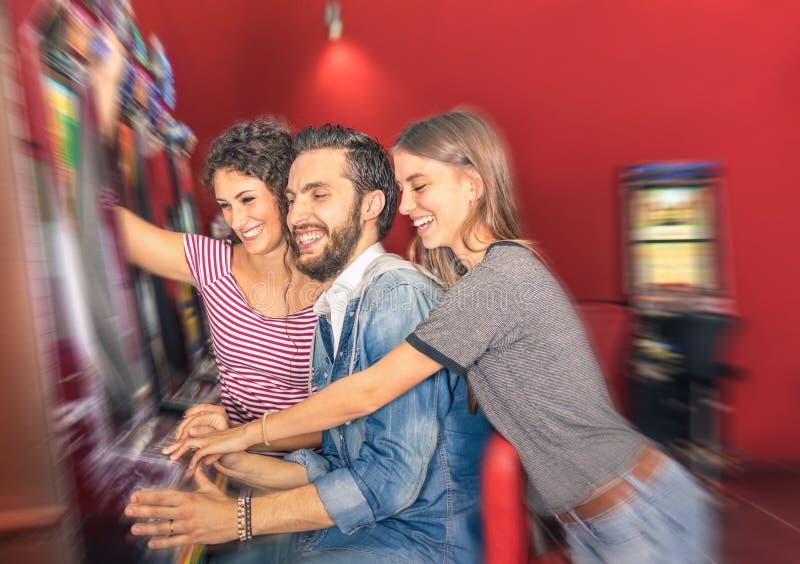 Amigos jovenes felices que se divierten así como la máquina tragaperras fotografía de archivo