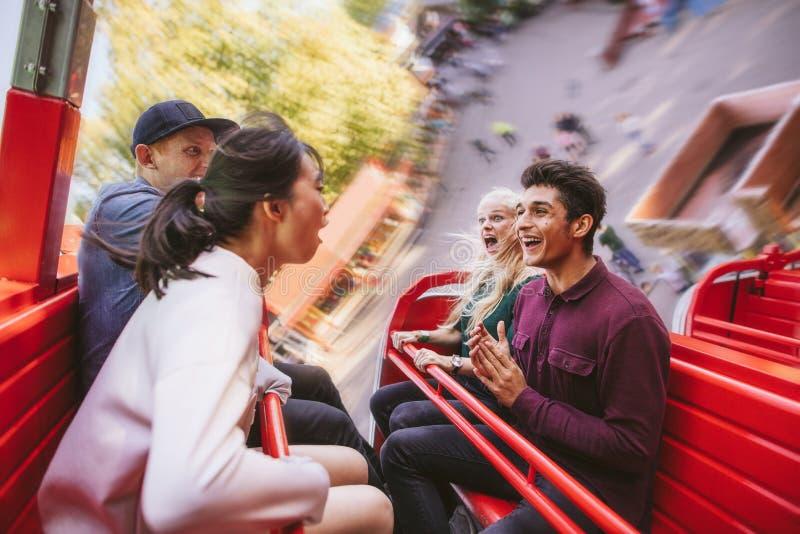 Amigos jovenes felices que se divierten en paseo del parque de atracciones imagenes de archivo
