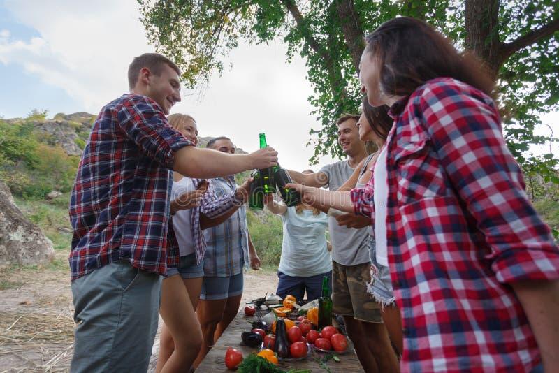 Amigos jovenes felices que tienen comida campestre en el parque Los amigos beben la cerveza en una comida campestre del verano en foto de archivo libre de regalías
