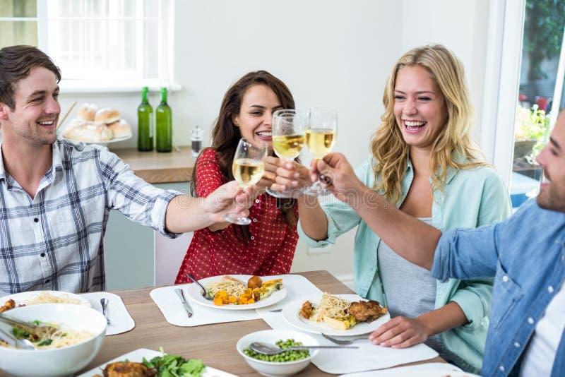 Amigos jovenes felices que tuestan el vino blanco imágenes de archivo libres de regalías