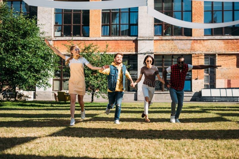 amigos jovenes multiculturales que llevan a cabo las manos mientras que divirtiéndose junto imagen de archivo libre de regalías