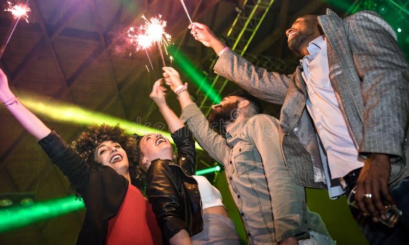 Amigos jovenes multirraciales que bailan en el club de noche con la bengala fi foto de archivo