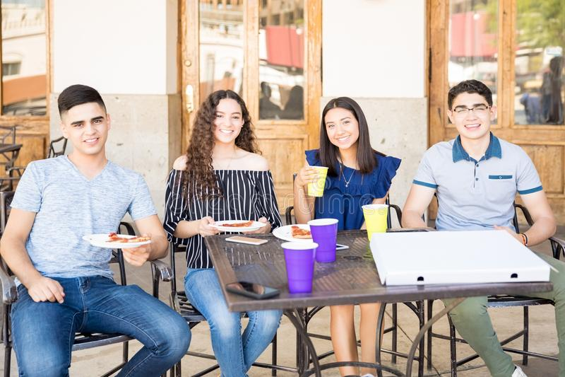 Amigos jovenes que comen café y pizza en el restaurante imagen de archivo