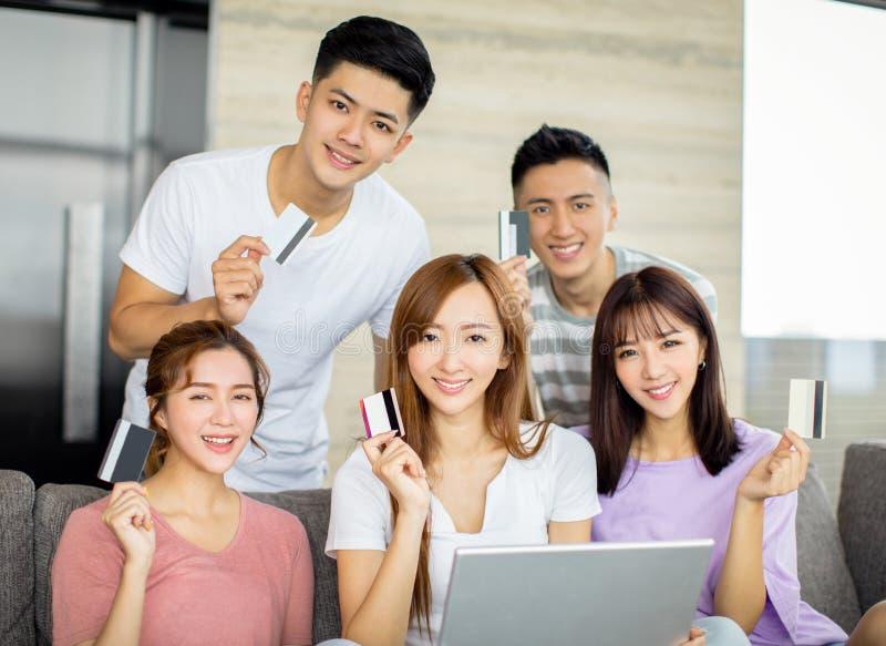 Amigos jovenes que compran en línea con la tarjeta de crédito y el ordenador portátil fotografía de archivo libre de regalías