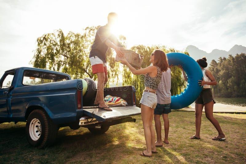 Amigos jovenes que descargan la camioneta pickup en acampada foto de archivo libre de regalías